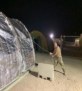 Man putting up a tent.