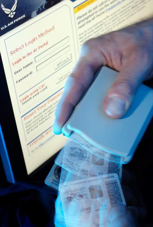 A hand holds a card reader and a common access card.