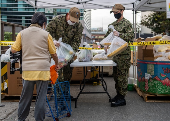 Sailors dispense food during a San Francisco Fleet Week 2021 community service project at SF-Marin Food Bank.