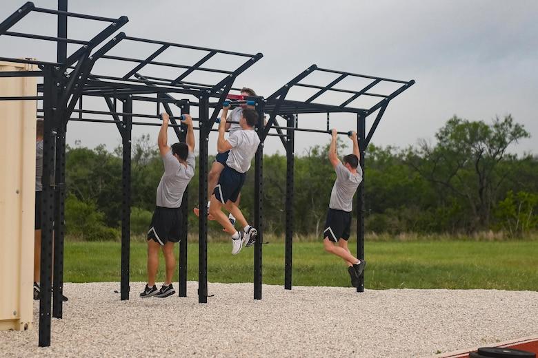 Three Airmen performing pullups