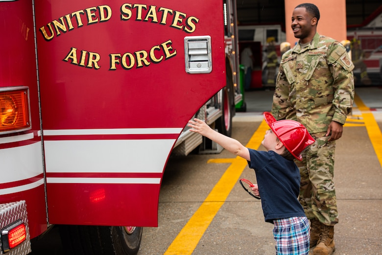 Senior Airman Tasheem Saunders, 51st Civil Engineer Squadron, fire emergency services driver operator, assists children getting in and out of a firetruck during a Fire Prevention Week open house event at Osan Air Base, Republic of Korea, Oct. 9, 2021.