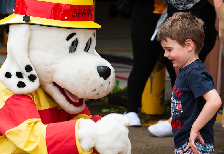 Sparky, the 51st Fighter Wing Fire Department mascot, greets a child during a Fire Prevention Week open house event at Osan Air Base, Republic of Korea, Oct. 9, 2021.