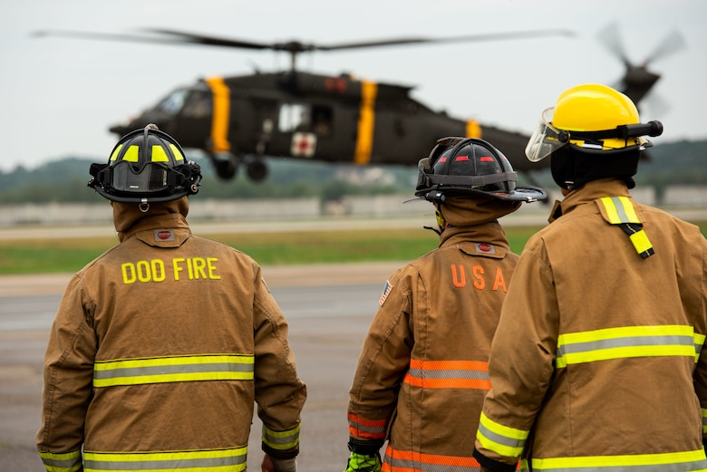Airmen from the 51st Civil Engineer Squadron prepare for a simulated helicopter extraction during a Fire Prevention Week open house event at Osan Air Base, Republic of Korea, Oct. 9, 2021.