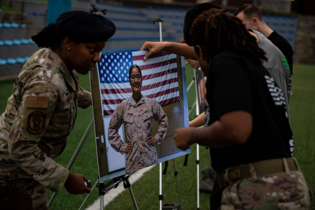 51st Security Forces Squadron members place the picture of U.S. Marine Corps Sgt. Johanny Rosario Pichardo during a memorial ruck march.