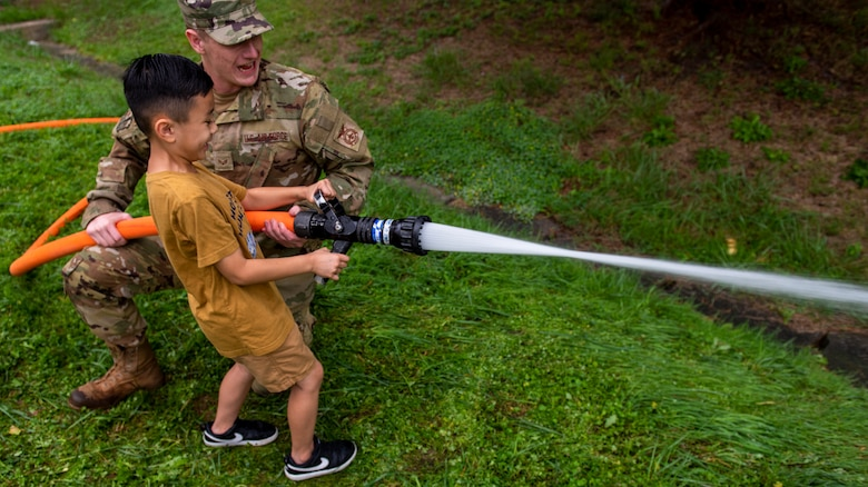 A 51st Civil Engineer Squadron fireman helps a child attendee use a fire hose during the Fire Prevention Week's Kids Showcase