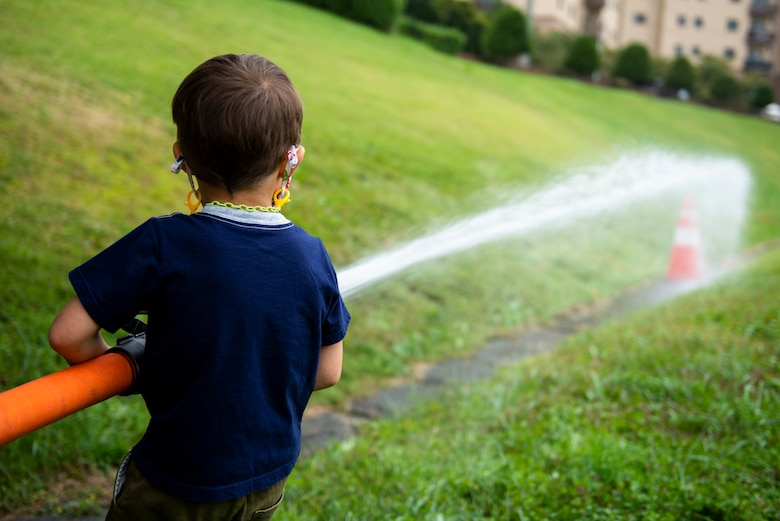 A child attendee uses a fire hose during the Fire Prevention Week's Kids Showcase