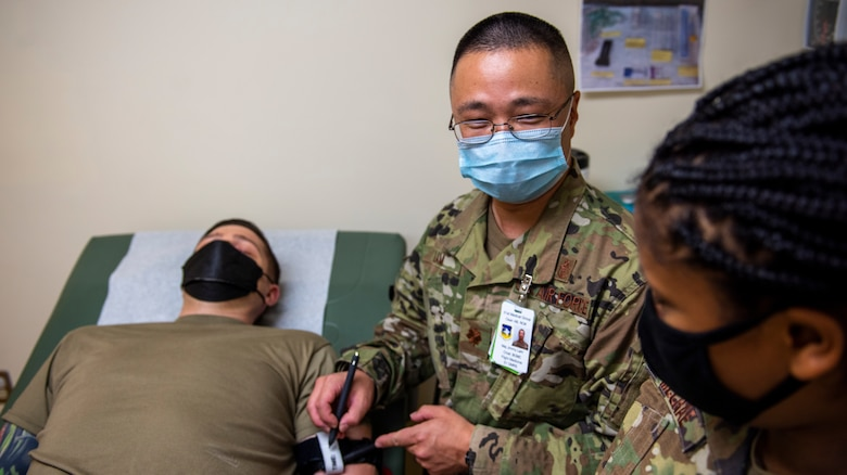 Maj. Jimmy Lam, 51st Operational Medical Readiness Squadron base operational medical clinic chief, shows a physician assistant how to apply a tourniquet