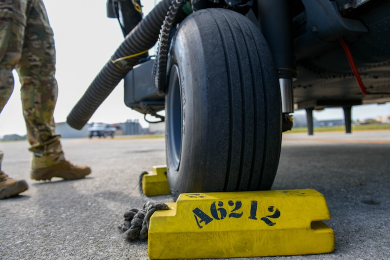 A U.S. Air Force Airman assigned to the 56th Rescue Squadron prepare an HH-60G Pave Hawk A6212 for its final sortie at Aviano Air Base, Italy, Sept. 23, 2021. Wheel chocks are wedges of sturdy material placed closely against a vehicle's wheels to prevent accidental movement and are placed for safety in addition to setting the brakes. (U.S. Air Force photo by Senior Airman Brooke Moeder)