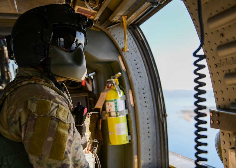 U.S. Air Force Staff Sgt. Kinga Hudson, 56th Rescue Squadron special missions aviator, looks out of an HH-60G Pave Hawk's window during its final sortie, Sept. 23, 2021. There are five helicopters assigned to the 56th RQS with two retiring by the end of 2021. (U.S. Air Force photo by Senior Airman Brooke Moeder)