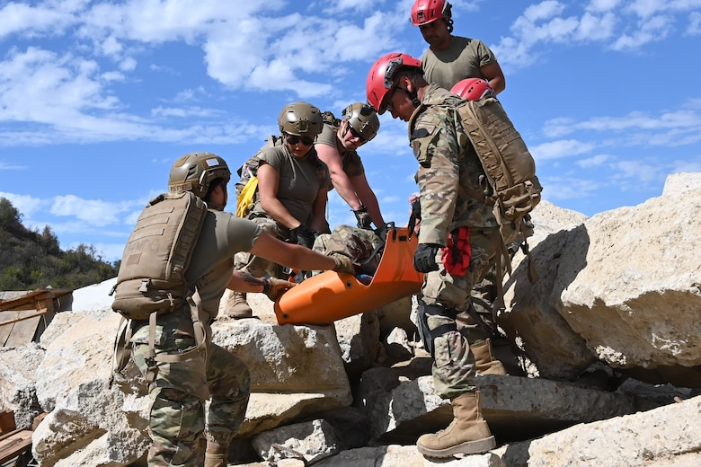 Members from the 118th Medical Group (MDG), Tennessee Air National Guard, carry a stretcher during a search and rescue exercise Sept. 12, 2021 in Ventura, California. 118th MDG members traveled to California to simulate an earthquake scenario, and get training on their new En-Route Patient Stating System capabilities. (U.S. Air National Guard photo by Master Sgt. Jeremy Cornelius)