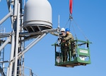 Information System Technician 2nd Class Nathan A. Milca, right, and Electronics Technician 2nd Class Drake W. Childers perform annual maintenance on the forward house antennae aboard the Expeditionary Sea Base USS Hershel