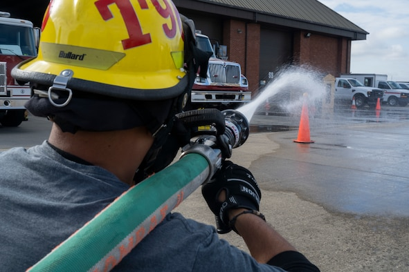A Team Mildenhall Airman sprays a target with a hose in the 'charged line advancement' event during the 2021 Fire Muster Challenge at Royal Air Force Mildenhall, England, Oct. 7, 2021. The 100th Civil Engineer Squadron held the challenge to spread the message of fire safety during Fire Prevention Week. (U.S. Air Force photo by Airman Alvaro Villagomez)