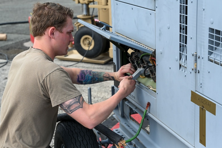 Staff Sgt. Colton Neal, 49th Aircraft Maintenance Squadron MQ-9 ground control station supervisor, wires equipment to a generator, Sept. 11, 2021, on Marine Corps Base Hawaii. Generators were used to power a ground control station, a containerized dual control segment, and multiple ground data terminals. (U.S. Air Force photo by Airman 1st Class Adrian Salazar)