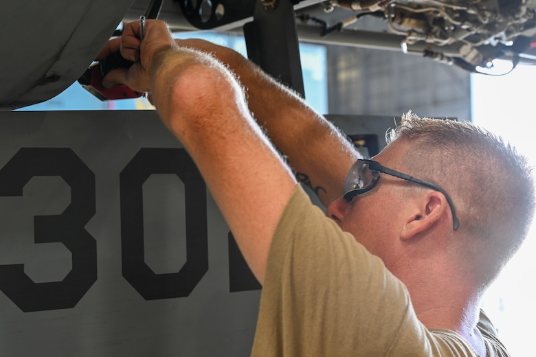"""Master Sgt. Chance Cole, special mission aircraft program manager, builds an MQ-9 Reaper, Sept. 11, 2021, on Marine Corps Base Hawaii. Multiple MQ-9s were disassembled and placed in a """"coffin"""" container for sealift transport to be used in Exercise Agile Combat Employment Reaper. (U.S. Air Force photo by Airman 1st Class Adrian Salazar)"""