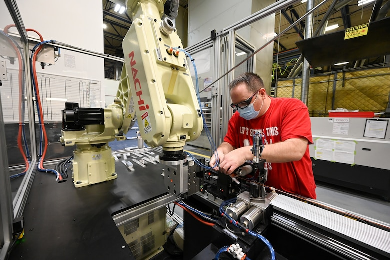 Matthew Noorda, 526th Electronics Maintenance Squadron, prepares an automated forming machine for operation at Hill Air Force Base, Utah, Sept. 24, 2021. The 526th EMXS replaced its process of winding and forming coils by hand with automated equipment in order to save time and money while improving product quality and shop safety. (U.S. Air Force photo by R. Nial Bradshaw)