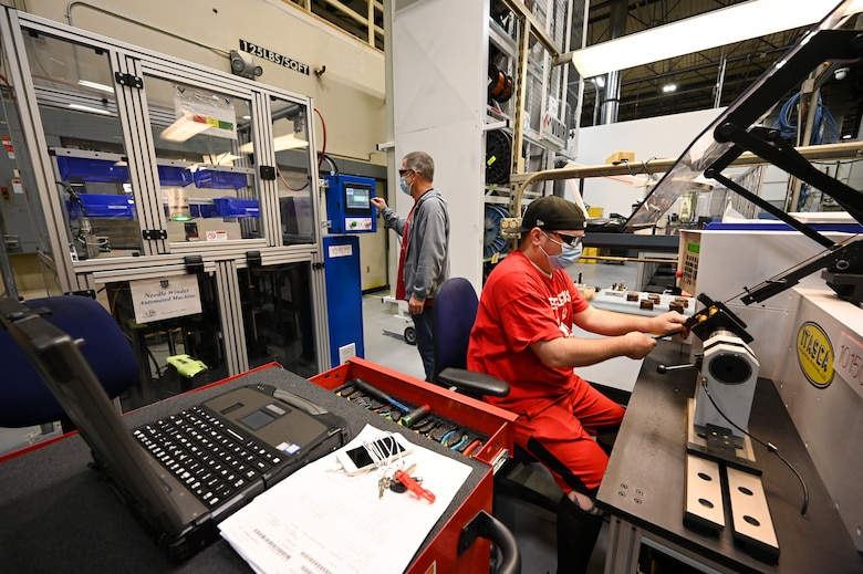 Matthew Noorda, right, and Michael Sherman, 526th Electronics Maintenance Squadron, operate automated winding equipment at Hill Air Force Base, Utah, Sept. 24, 2021. The 526th EMXS replaced its process of winding and forming coils by hand with automated equipment in order to save time and money while improving product quality and shop safety. (U.S. Air Force photo by R. Nial Bradshaw)