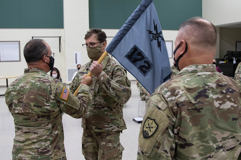 Brig. Gen. Jeffrey Terrill, director of the joint staff for the Michigan National Guard, hands the guidon of Detachment 1, Cyber Protection Team 172 (CPT 172), to Maj. Roman Kocherovsky, incoming CPT 172 commander, at a change of command ceremony at Joint Forces Headquarters in Lansing, Mich., October 3, 2021. Outgoing CPT 172 commander, Lt. Col. Robert Maciolek, right, looks on as his former guidon is relinquished (U.S. Army National Guard photo by Capt. Joe Legros)