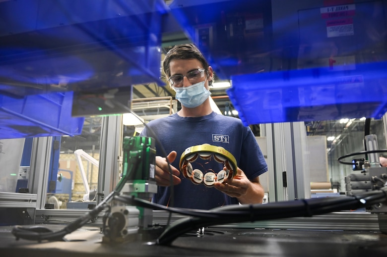 Draven Lee, 526th Electronics Maintenance Squadron, removes coils from an automated winding machine at Hill Air Force Base, Utah, Sept. 9, 2021. The 526th EMXS replaced its process of winding and forming coils by hand with automated equipment in order to save time and money while improving product quality and shop safety. (U.S. Air Force photo by R. Nial Bradshaw)