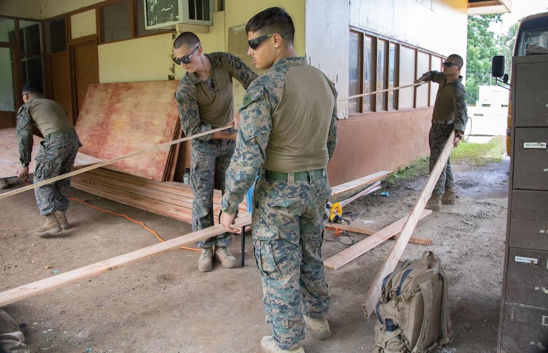 U.S. Marine Corps combat engineers with Task Force Koa Moana 21, I Marine Expeditionary Force, move wood beams to be cut at Ngeremlengui Elementary School in Ngeremlengui, Republic of Palau, Oct. 2, 2021. Task Force Koa Moana 21 provides a unique opportunity to enhance relationships with the Republic of Palau.
