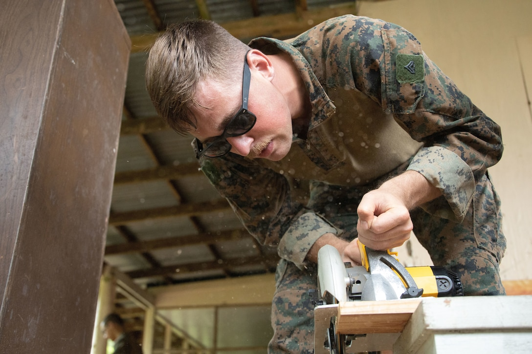 U.S. Marine Corps Cpl. Tyler Illingworth, a combat engineer with Task Force Koa Moana 21, I Marine Expeditionary Force, cuts plywood at Ngeremlengui Elementary School in Ngeremlengui, Republic of Palau, Oct. 2, 2021. Task Force Koa Moana 21 is a unifying mission that fosters enduring cooperation between the United States and the Republic of Palau.