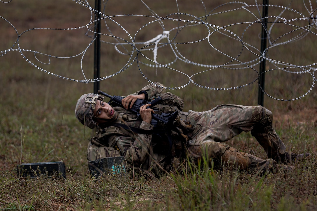 A soldier carrying a weapon lays on the ground and moves under razor wire.