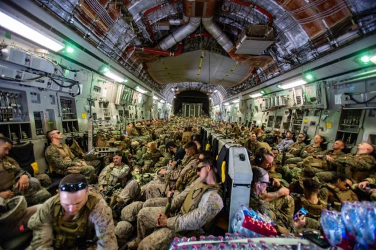 Marines sleep in a crowded plane.