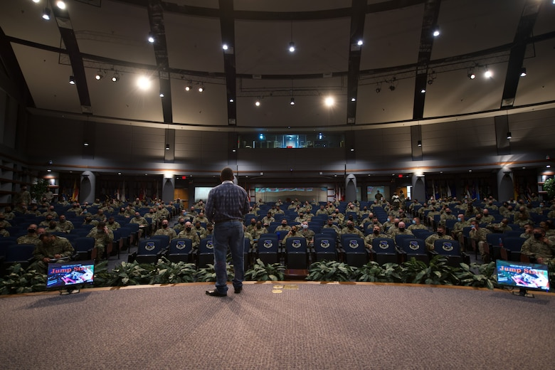 Photo of a speaker addressing students attending the SNCOA in a large auditorium.