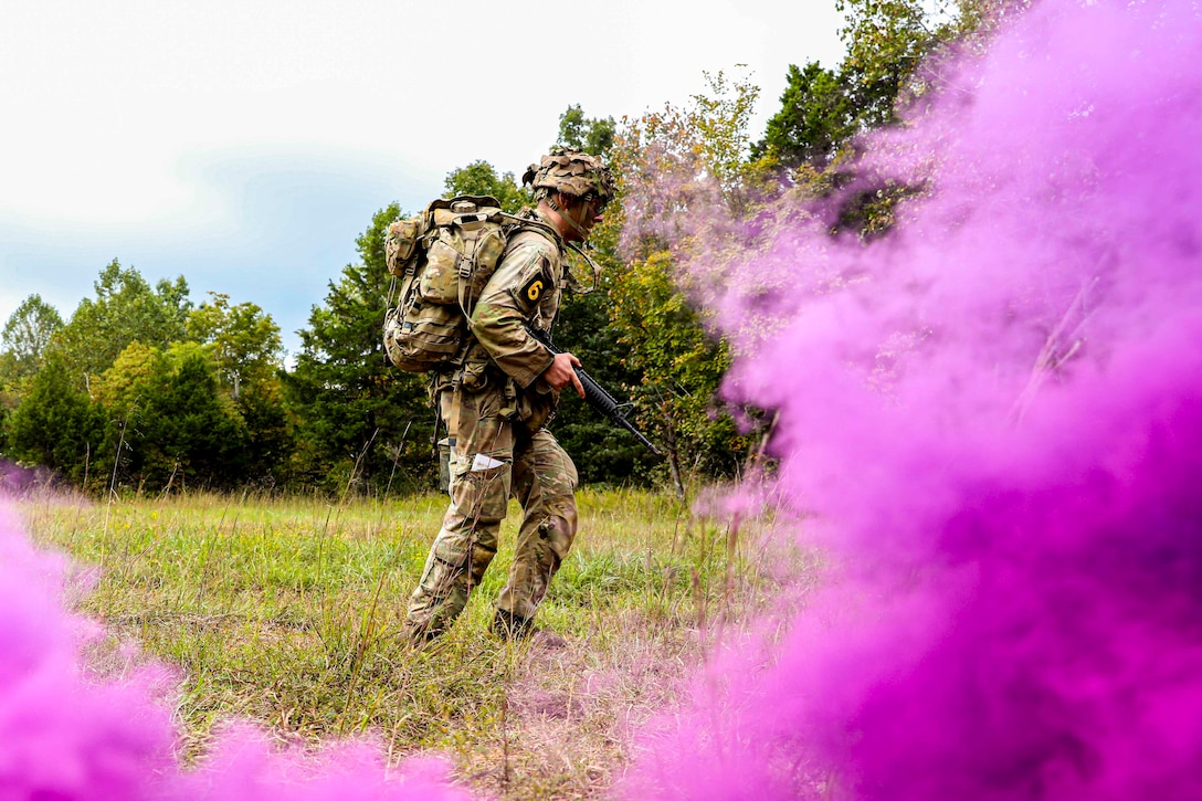 A soldier moves through a grassy field as purple smoke surrounds him.