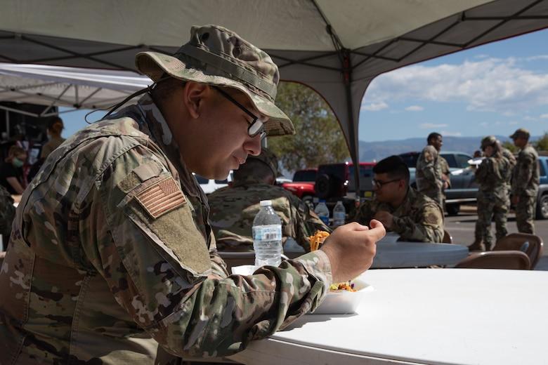 An Airman assigned to Task Force Holloman eats a free meal prepared by volunteers from Mountain View Church on Holloman Air Force Base, New Mexico, Oct. 5, 2021. The Department of Defense, through the U.S. Northern Command, and in support of the Department of State and Department of Homeland Security, is providing transportation, temporary housing, medical screening, and general support for at least 50,000 Afghan evacuees at suitable facilities, in permanent or temporary structures, as quickly as possible. This initiative provides Afghan evacuees essential support at secure locations outside Afghanistan. (U.S. Army photo by Spc. Nicholas Goodman)