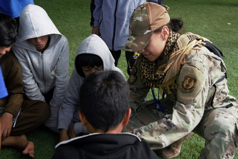 An Airman assigned to Task Force-Holloman interacts with Afghan children at Holloman Air Force Base, New Mexico, Oct. 1, 2021. The Department of Defense, through U.S. Northern Command, and in support of the Department of State and Department of Homeland Security, is providing transportation, temporary housing, medical screening, and general support for at least 50,000 Afghan evacuees at suitable facilities, in permanent or temporary structures, as quickly as possible. This initiative provides Afghan evacuees essential support at secure locations outside Afghanistan. (U.S. Navy photo by Mass Communications Specialist 1st Class Sarah Rolin)