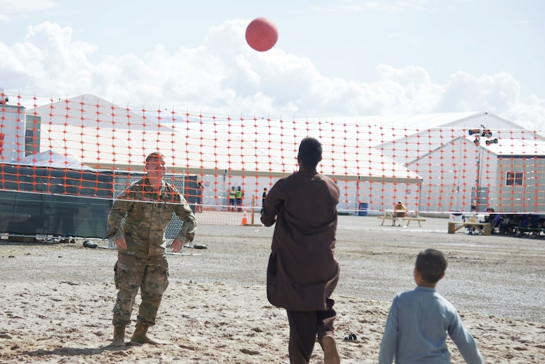 An Afghan boy serves the ball to an awaiting Soldier attached to Task Force-Holloman during an impromptu volleyball game at Holloman Air Force Base, New Mexico, Oct. 1, 2021. The Department of Defense, through U.S. Northern Command, and in support of the Department of State and Department of Homeland Security, is providing transportation, temporary housing, medical screening, and general support for at least 50,000 Afghan evacuees at suitable facilities, in permanent or temporary structures, as quickly as possible. This initiative provides Afghan evacuees essential support at secure locations outside Afghanistan. (U.S. Navy photo by Mass Communications Specialist 1st Class Sarah Rolin)