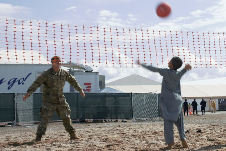 An intense volleyball game ensues between a Soldier assigned to Task Force-Holloman and an Afghan boy on Aman Omid Village on Holloman Air Force Base, New Mexico, Oct. 1, 2021. The Department of Defense, through U.S. Northern Command, and in support of the Department of State and Department of Homeland Security, is providing transportation, temporary housing, medical screening, and general support for at least 50,000 Afghan evacuees at suitable facilities, in permanent or temporary structures, as quickly as possible. This initiative provides Afghan evacuees essential support at secure locations outside Afghanistan. (U.S. Navy photo by Mass Communications Specialist 1st Class Sarah Rolin)