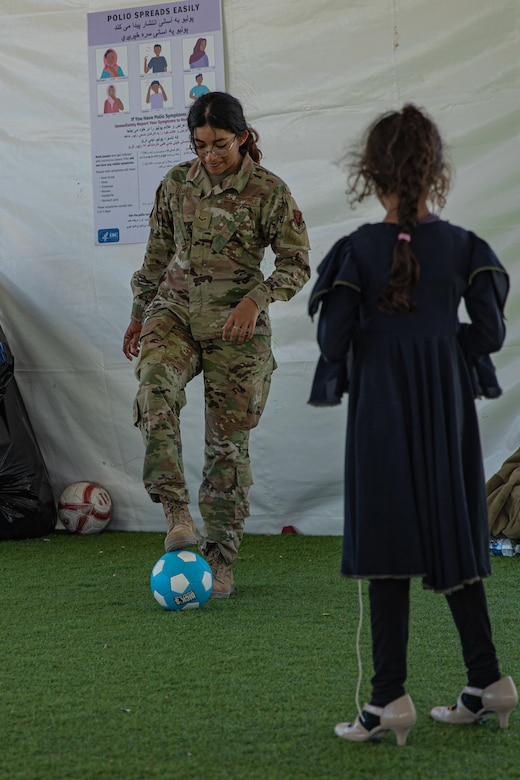An Airman attached to Task Force-Holloman plays soccer with an Afghan child at Aman Omid Village on Holloman Air Force Base, New Mexico, Oct. 7, 2021. The Department of Defense, through U.S. Northern Command, and in support of the Department of Homeland Security, is providing transportation, temporary housing, medical screening, and general support for at least 50,000 Afghan evacuees at suitable facilities, in permanent or temporary structures, as quickly as possible. This initiative provides Afghan personnel essential support at secure locations outside Afghanistan. (U.S. Army photo by Pfc. Anthony Sanchez)