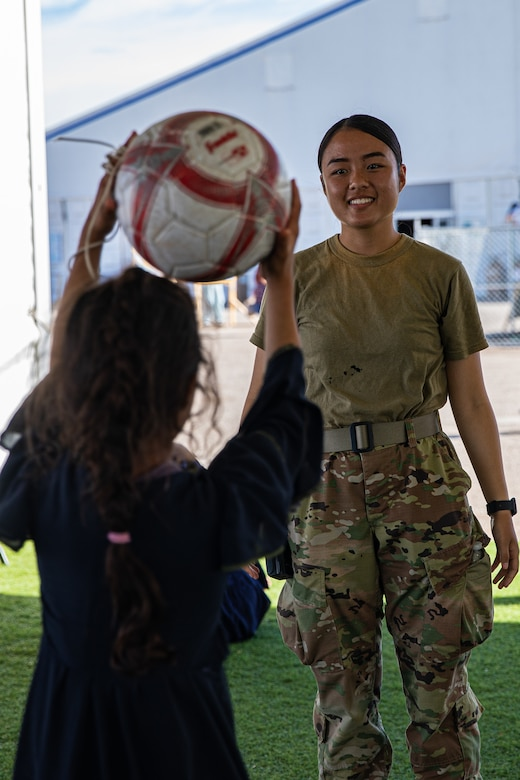 An Airman attached to Task Force-Holloman plays catch with an Afghan child at Aman Omid Village on Holloman Air Force Base, New Mexico, Oct. 7, 2021. The Department of Defense, through U.S. Northern Command, and in support of the Department of Homeland Security, is providing transportation, temporary housing, medical screening, and general support for at least 50,000 Afghan evacuees at suitable facilities, in permanent or temporary structures, as quickly as possible. This initiative provides Afghan personnel essential support at secure locations outside Afghanistan. (U.S. Army photo by Pfc. Anthony Sanchez)
