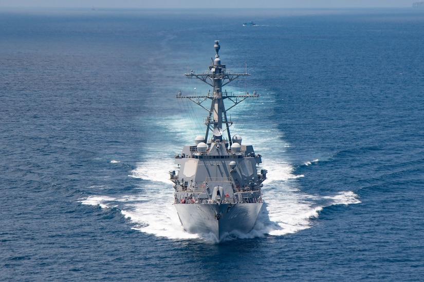 A navy ship moves through the water.
