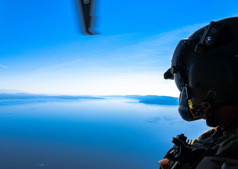 U.S. Air Force Master Sgt. Steven Prather, 56th Rescue Squadron operations superintendent, peers out the door of an HH-60G Pave Hawk A6212's during its final flight in Croatia, Sept. 23, 2021. For more than 30 years, A6212 has been assigned exclusively to the 56th RQS. In September 2021, the helicopter is the first aircraft to retire out of the 56th with the plan to become a static display. (U.S. Air Force photo by Senior Airman Brooke Moeder)