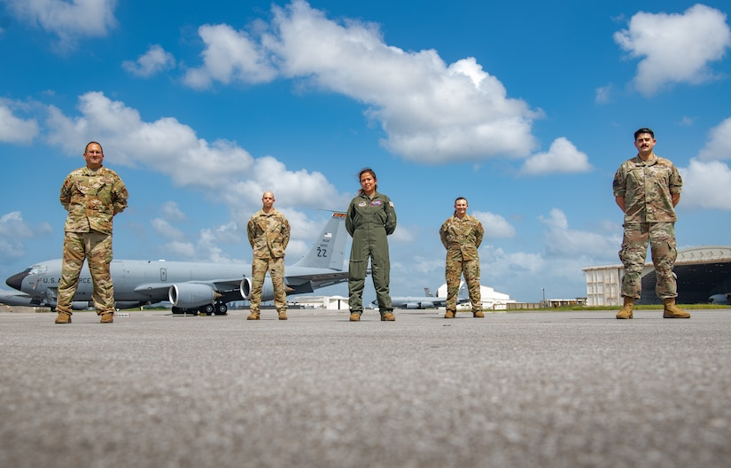 Five U.S. Air Force service members pose for a photo.