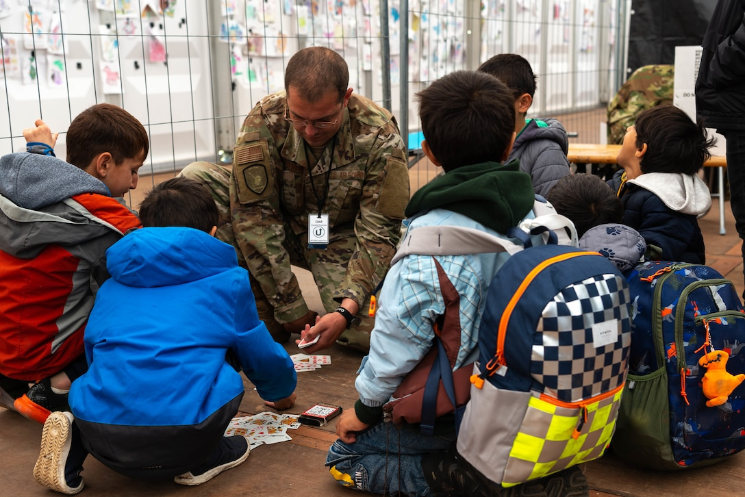 Airman plays cards with evacuees.