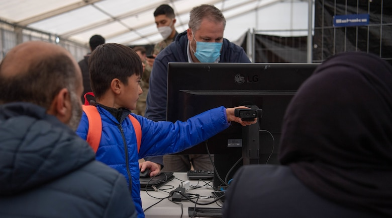 Evacuee helps takes photo of family at check point.