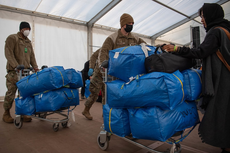 Airmen collect evacuee luggage.