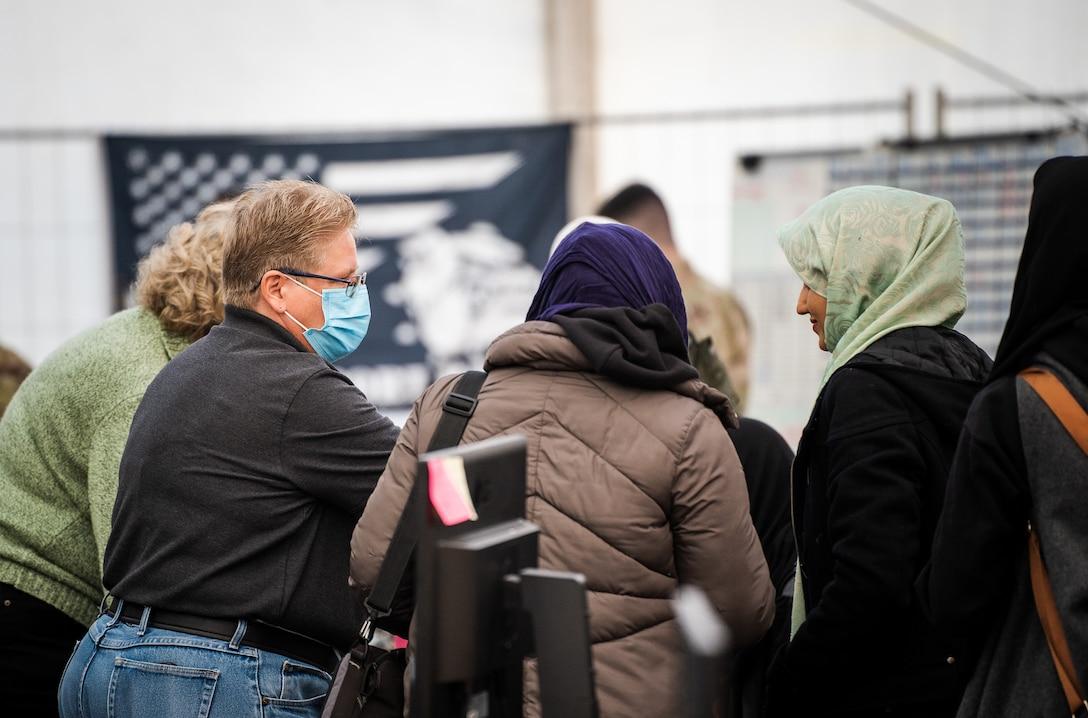 Transportation Security Administration employee helps process evacuees through passenger terminal.