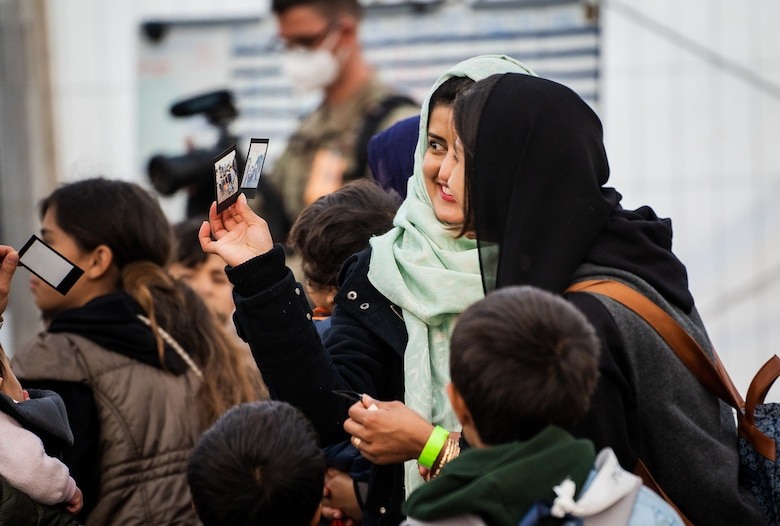 Evacuees look at photos of themselves.