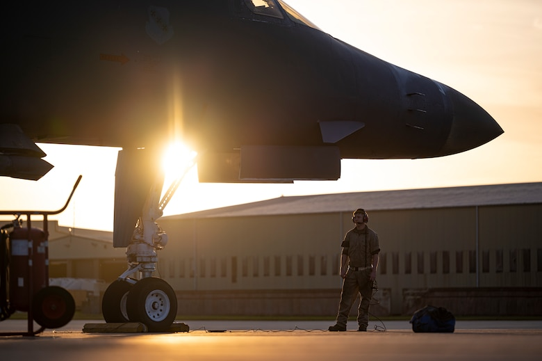 A crew chief assigned to the 9th Expeditionary Bomb Squadron waits while a B-1B Lancer is refueled at RAF Fairford, United Kingdom, Oct. 11, 2021. Petroleum, oil and lubrication Airmen conducted a hot pit refueling at Spangdahlem Air Base, Germany, following its return from a Bomber Task Force Europe mission over the Baltic Sea region to allow aircrew to support a local training mission with Lithuanian forces. (U.S. Air Force photo by Airman 1st Class Josiah Brown)