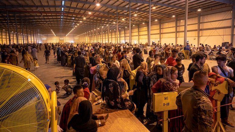 Afghanistan evacuees line up for supplies at one of the operating locations, Aug. 23, 2021, at Al Udeid Air Base, Qatar.