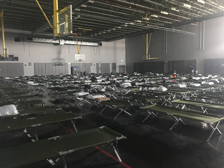 Cots are spread out on a basketball court at one of the gyms at Al Udeid Air Base, Qatar.