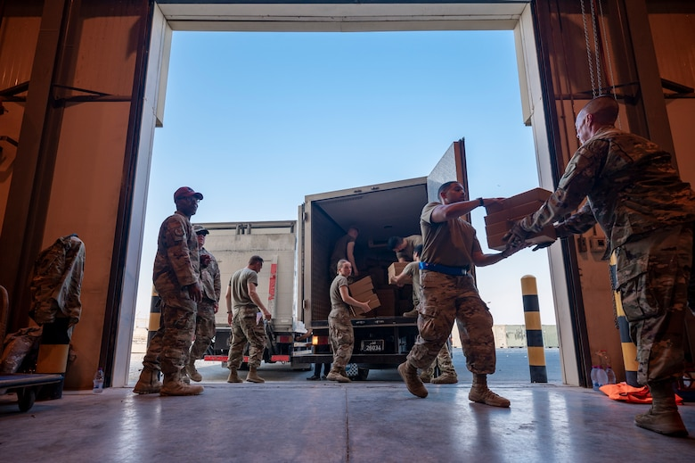 Airmen unload food from a truck for Afghanistan evacuees, Aug. 23, 2021, at Al Udeid Air Base, Qatar.