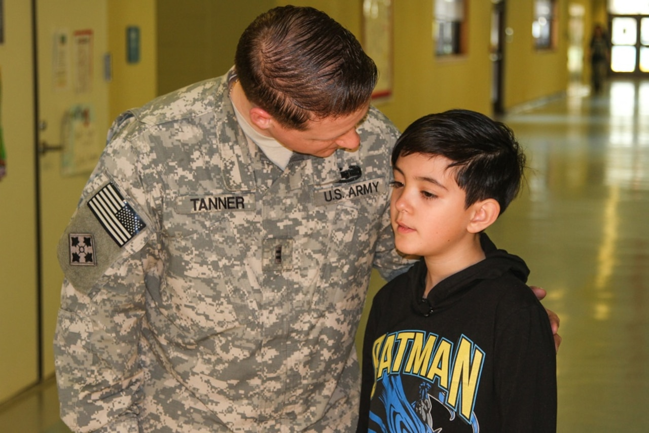 A soldier has his arm on the shoulder of a young boy as he leans forward to speak to the boy.
