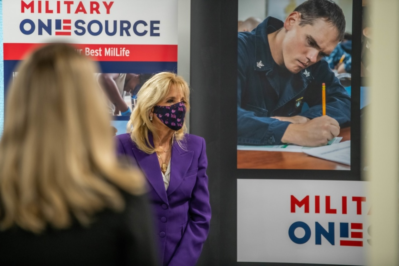 First Lady Dr. Jill Biden stands in front of a Military OneSource sign at an event.