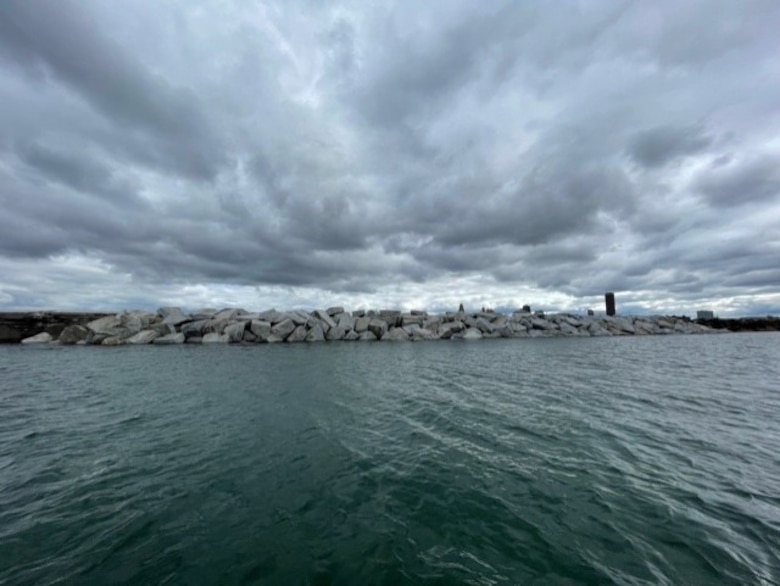 Large rocks piled to form a breakwater in water, with a city skyline in the background.