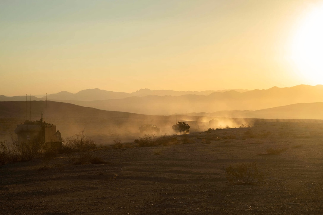 Army vehicles drive in a line through a desert.(